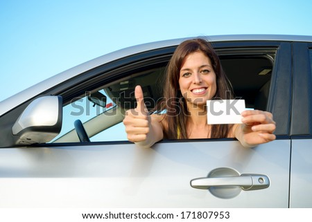 Female young car driver going thumbs up after passing the driving license test. Successful woman showing blank card and smiling in vehicle. - stock photo