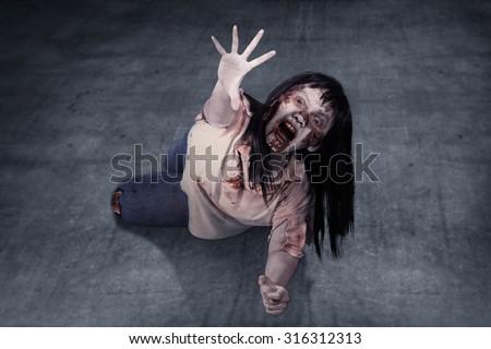 Female zombie crouching on the floor. Halloween concept - stock photo