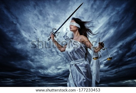 Femida, Goddess of Justice, with scales and sword wearing blindfold against dramatic stormy sky - stock photo