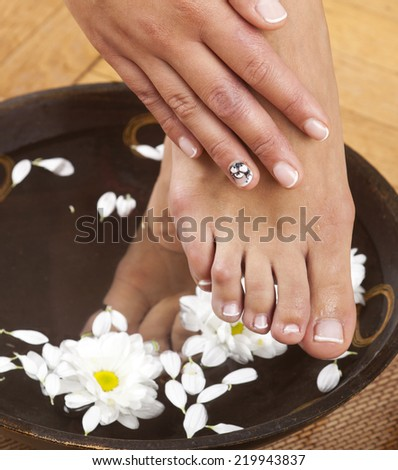 Feminine feet in foot spa bowl with flowers and hand - stock photo