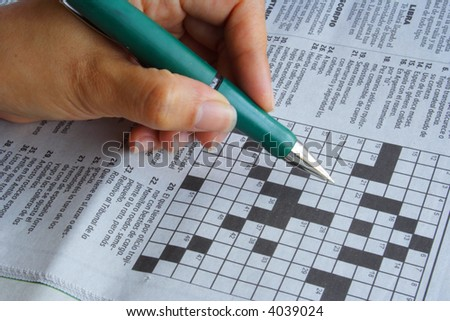 Feminine hand doing the crossword in the news paper - stock photo