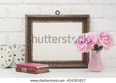 feminine mock-up with vintage frame and pink flowers on a white desk - stock photo