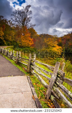 Fence and autumn color along the Blue Ridge Parkway in Julian Price Park, North Carolina. - stock photo