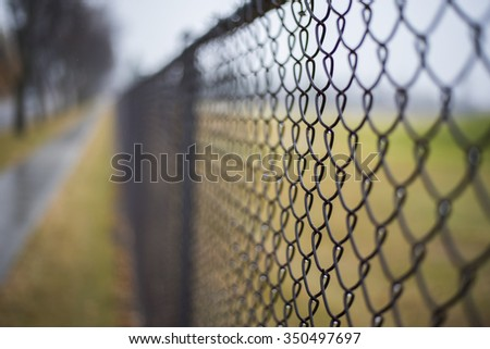 fence during rainy and overcast fall day, with shallow depth of field.  - stock photo