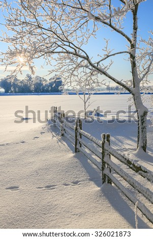 Fence in winter landscape - stock photo
