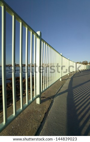 Fence lines the Cliff Walk, Cliffside Mansions of Newport Rhode Island - stock photo