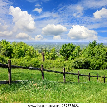 fence on green meadow in nice summer day - stock photo