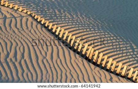 fence shadows and sand ripples on beach - stock photo