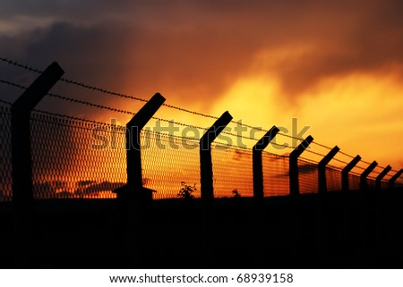 fence under sleeping sunset - stock photo