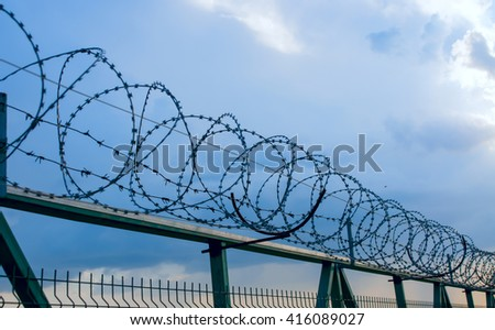 fence with barbed wire against the sky - stock photo