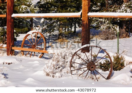 Fence with wagon wheels in snow - stock photo