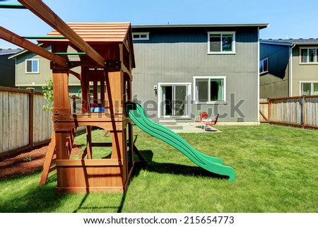 Fenced backyard with wooden playground for kids - stock photo