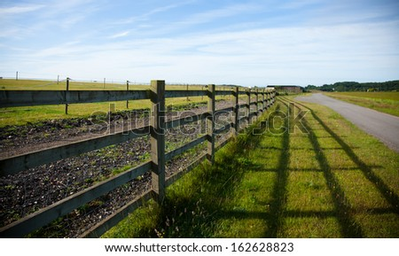 Fenced horse field with strong shadow - stock photo