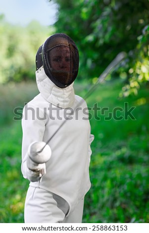 Fencer woman staying over beautiful nature background with rapier - stock photo