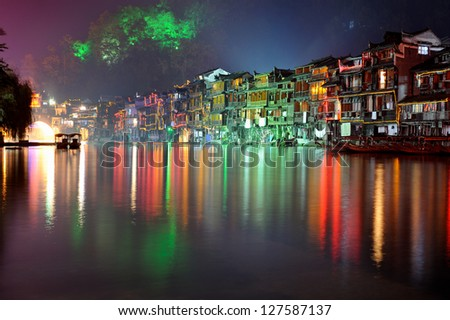 Fenghuang (Phoenix in English), small touristic town in Hunan province in China. Illuminated ancient buildings at night - stock photo