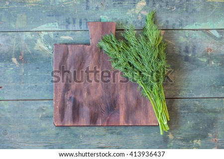 fennel bunch on a kitchen board on an old wooden background, selective focus - stock photo