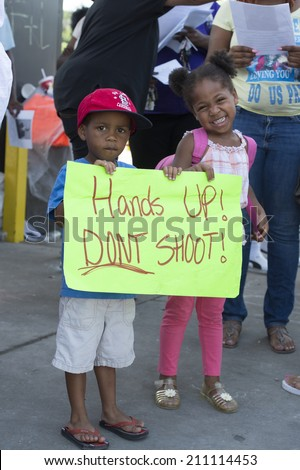 FERGUSON, MO/USA -AUGUST 15, 2014: Children hold sign at the Site of Quick Trip after Police Chief Thomas Jackson release of the name of the officer that shot Michael Brown. - stock photo