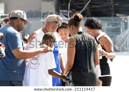 FERGUSON, MO/USA -  AUGUST 15, 2014: Group prays at the site of destroyed Quick Trip after Police Chief Thomas Jackson release of the name of the officer that shot Michael Brown. - stock photo