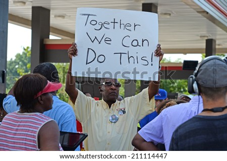 FERGUSON, MO/USA -  AUGUST 15, 2014: Man holds sign at the site of Quick Trip after Police Chief Thomas Jackson release of the name of the officer that shot Michael Brown. - stock photo