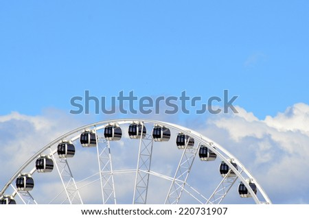 Ferris wheel against blue sky with white clouds. copy space. Concept photo: leisure, activity, travel, recreational,  vacation, play, enjoyment, happiness, pleasure, game - stock photo