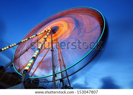 Ferris wheel and rollercoaster in motion at amusement park at night - stock photo