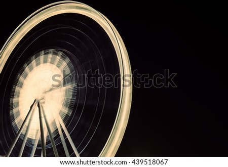 Ferris wheel in motion at amusement park at night  - stock photo