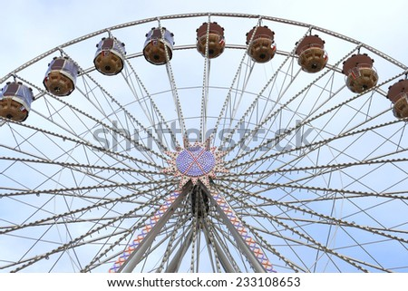 ferris wheel on a funfair against blue sky, frontal view  - stock photo