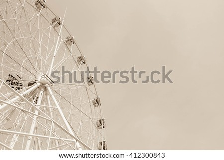 ferris wheel on blue sky and white cloud in sepia filter - stock photo