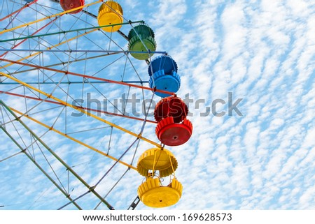 Ferris wheel on the blue cloudy sky background - stock photo