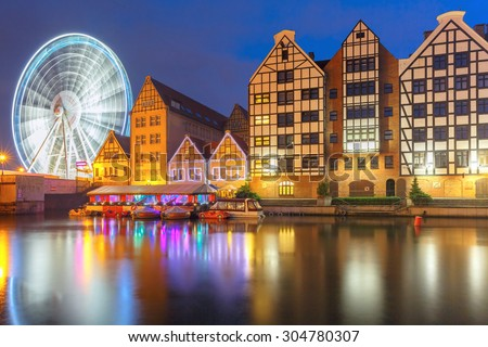 Ferris wheel with water reflection at Trade fair St Dominic in Old Town of Gdansk at night, Poland - stock photo