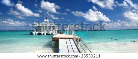 Ferry boat docked at a beautiful Caribbean tropical beach with white sand and green ocean, suitable background for a variety of designs - stock photo