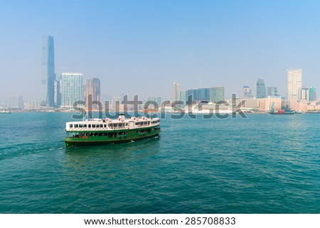 Ferry, crossing the channel to Kowloon, with a luxury cruise liner tied to the pier in the background. - stock photo