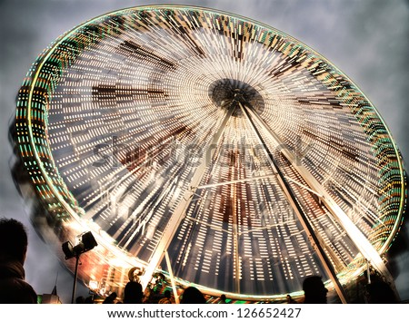 Ferry wheel with movement with light trail and with dark grey sky - stock photo