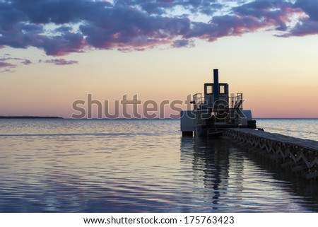 Ferryboat moored at pier in the evening - stock photo