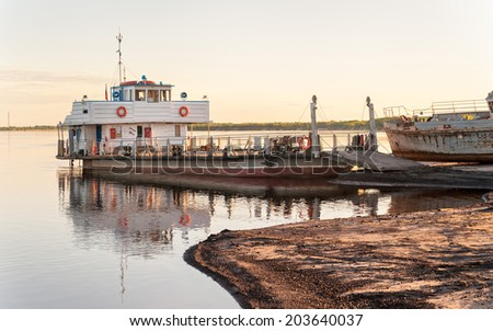 Ferryboat moored before old rusty ship on sand beach at sunset. Solvychegodsk, Arkhangelsky region, Russia.  - stock photo
