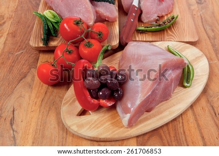 fersh raw turkey meat steak fillet with vegetables kale tomatoes lettuce red hot chili pepper and dark olives on cutting board over wooden table - stock photo
