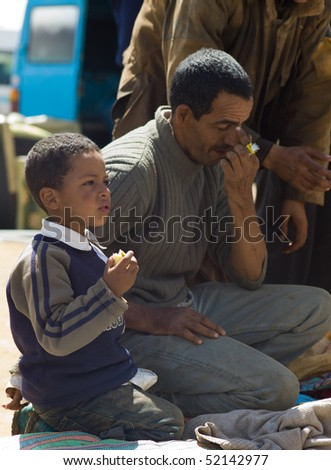 FES - APRIL 16: Father and son sell products at a market (souk) in a village near Fes in Morocco April 16, 2010 Fes, Morocco. - stock photo