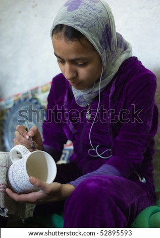 FES - APRIL 17: Islamic girl is painting ceramics in a pottery in Fes April 17, 2010 in Fes, Morocco. - stock photo