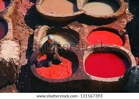 FES - FEBRUARY 02: Unidentified Morrocan man at working dying skins in a Fes tannery February 02, 2009 in Fes, Morocco. - stock photo