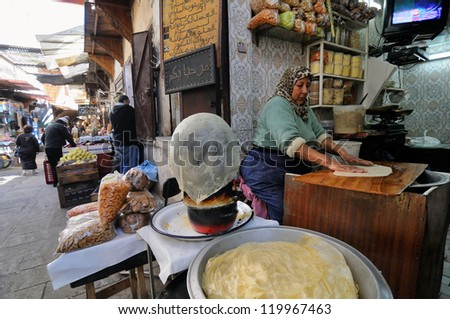 FES - MARCH 10: Unknown woman trades a traditional bread in a Market (souk) in a city Fes in Morocco. The market is one of the most important attractions of the city. March 10, 2012 Fes, Morocco. - stock photo