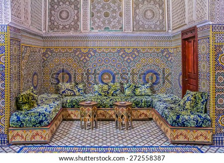 Fes, Morocco - May 11, 2013: Courtyard decorated with ornate mosaic and arabesque carvings, with traditional couches in a Moroccan riad - stock photo
