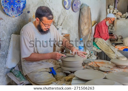 Fes, Morocco - May 11, 2013: Moroccan potter at work in a pottery shop - stock photo