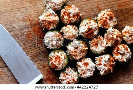 Festive appetizer hollow cucumber filled with king crab and garnished with paprika - stock photo