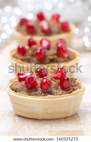 festive appetizer - tartlets with liver paste and pomegranate seeds, close-up, vertical - stock photo