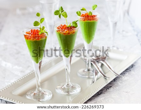 festive appetizer with avocado and pea puree and red caviar - stock photo