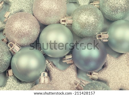 Festive background of aqua pale blue christmas glitter baubles and stars on a pale aqua blue material tablecloth background with retro vintage filter. - stock photo