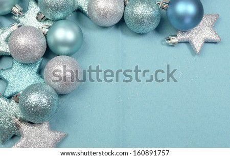 Festive background of aqua turquoise pale blue christmas glitter baubles and stars on a pale aqua blue material tablecloth background, with copy space, - stock photo