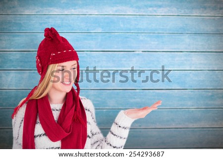 Festive blonde presenting with hand against wooden planks - stock photo