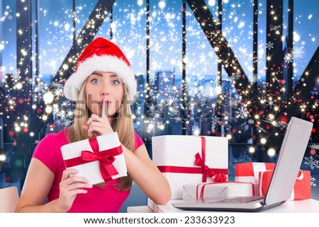 Festive blonde shopping online with laptop against glittering lights in room - stock photo