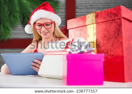 Festive blonde shopping online with tablet pc against festive bow over wood - stock photo